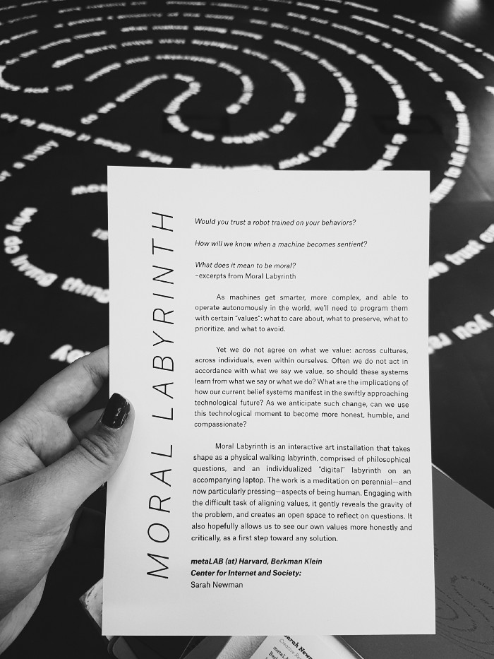 Photograph of the Moral Labyrinth leaflet along with its correspondent an art installation.