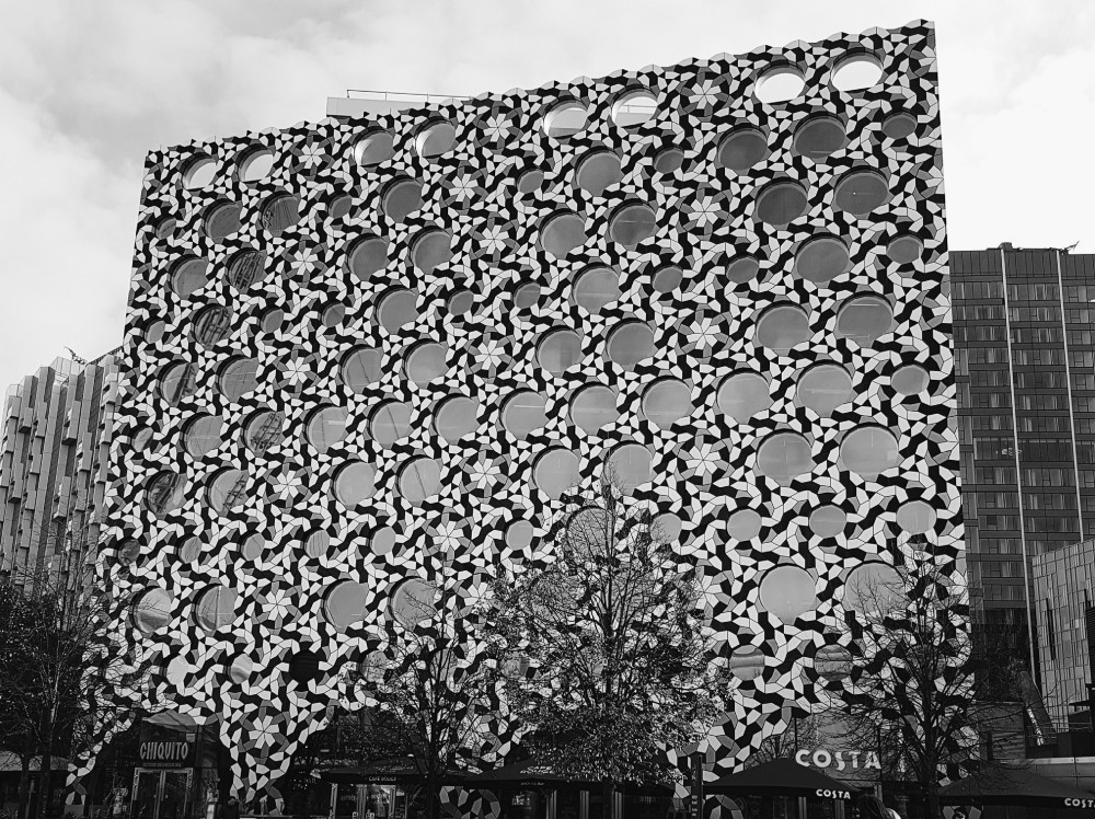 Photograph of the Ravensbourne University building, covered in tiles that together result in a really trippy pattern along with its round windows. That university is really close to The O2 Arena, and which makes getting there by tube or bus extremely easy.